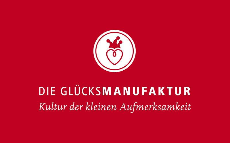 Logo DIE GLÜCKSMANUFAKTUR auf rotem Grund